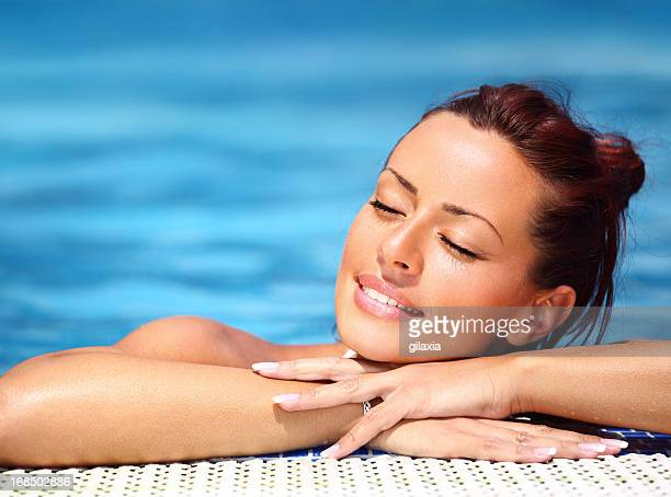 Woman relaxing at swimming pool.