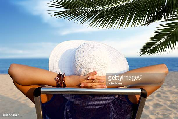 Woman relaxing at the beach, sitting on deck chair