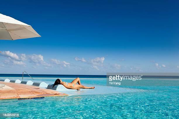 Femme détente au complexe touristique de la piscine à débordement de l'hôtel de Mexico
