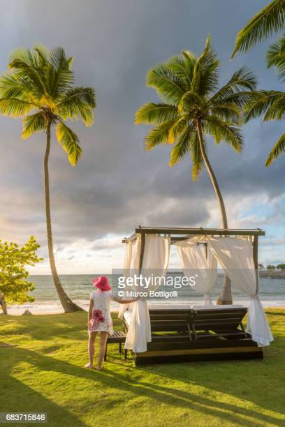 Woman relaxing by a beach bed at sunset. Dominican Republic.