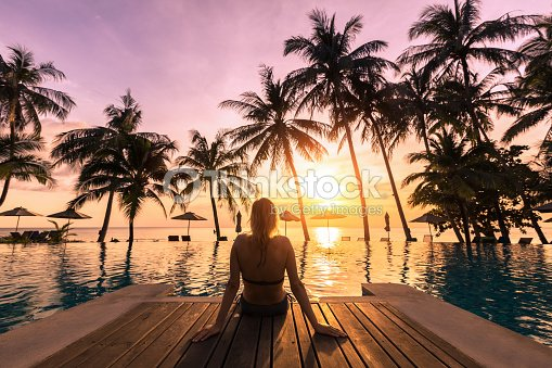 Woman relaxing by the pool in luxurious beachfront hotel resort : Stock Photo