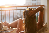 Woman relaxing at balcony enjoying sunrise. Good morning