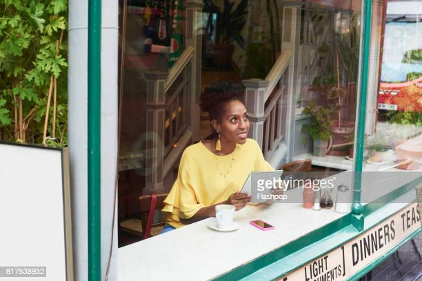 Woman relaxing in a cafe using digital tablet