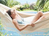 Woman relaxing in a hammock by a pool