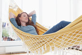 Woman relaxing in a hammock in her apartment