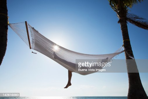 Woman relaxing in a hammock on the beach : Foto stock
