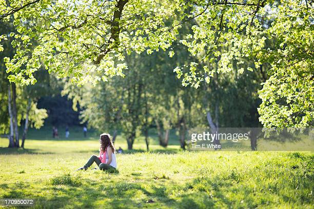 Woman relaxing in a meadow at sunset