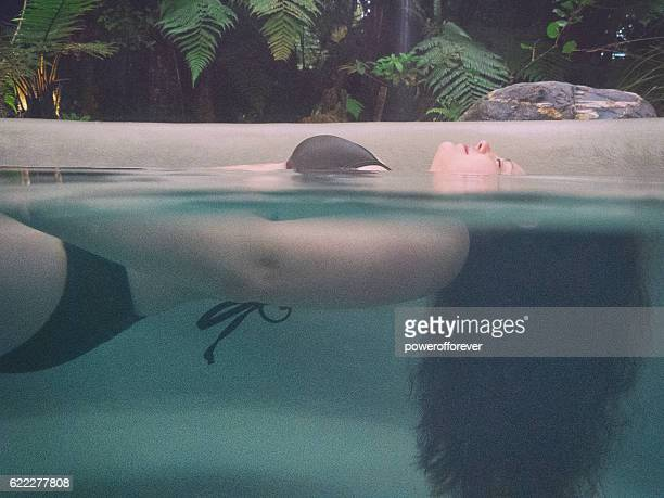 Woman relaxing in a rainforest hot spring, New Zealand