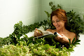 Woman relaxing in bathtub covered with plants, reading magazine