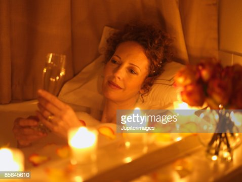 Woman relaxing in bathtub with champagne