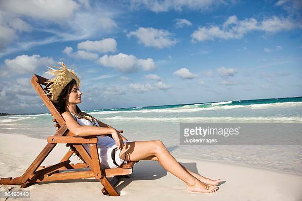 Woman relaxing in beach chair by the ocean