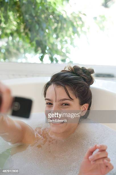 Woman relaxing in bubble bath using cellular phone and smiling