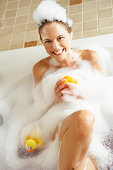 Woman Relaxing In Bubble Filled Bath