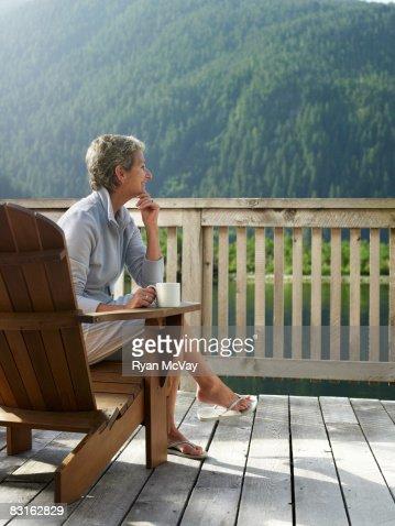 Mujer relajante en una silla en la terraza. : Foto de stock