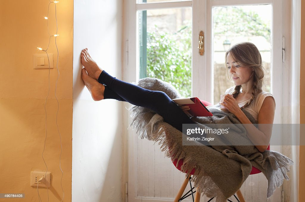 woman relaxing in chair, reading on digital tablet