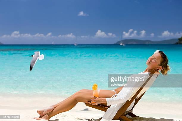 Frau entspannend auf Stuhl mit cocktail in der Karibik