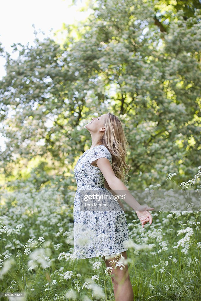 Woman relaxing in field of flowers : Stock Photo