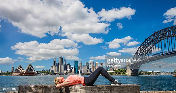 Woman relaxing in front of Sydney Harbor and city skyline