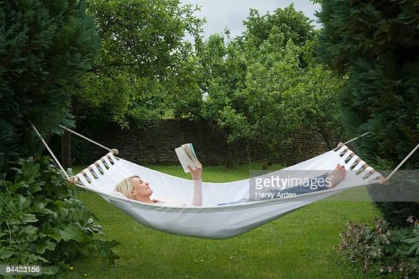 Woman relaxing in hammock in garden