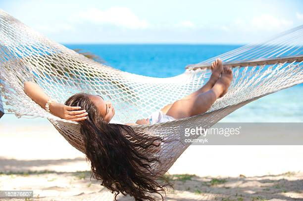 Woman relaxing in hammock on a beach