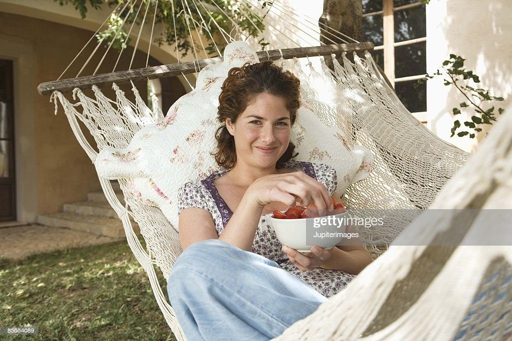 Woman relaxing in hammock with strawberries : Stock Photo