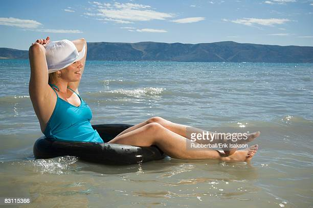 Woman relaxing in inner tube on lake