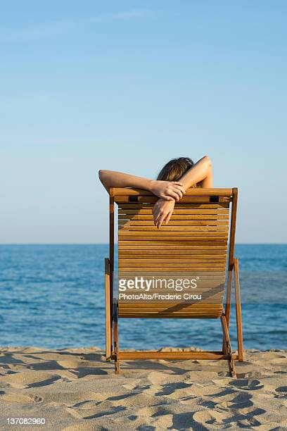 Woman relaxing in lounge chair on beach