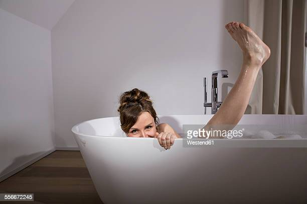 Woman relaxing in modern bathtub
