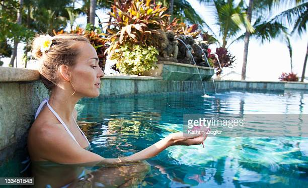 woman relaxing in pool, holding flower