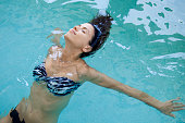 Woman relaxing in pool with eyes closed