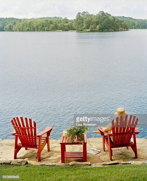 Woman relaxing in red Adirondack chair by lake