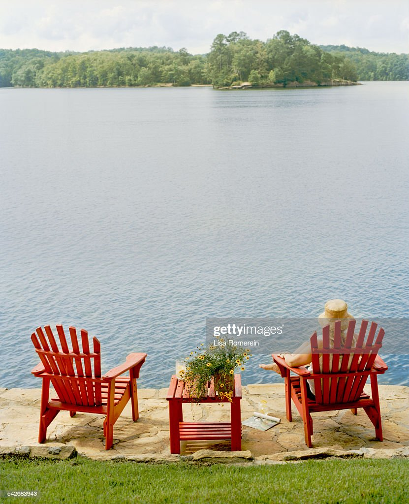 Superb Woman Relaxing In Red Adirondack Chair By Lake