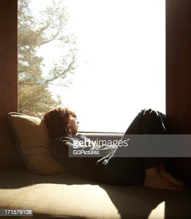 Mujer relajante en la ventana mirando hacia fuera en las nubes uso