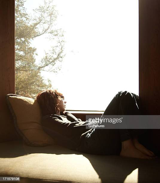 Woman relaxing in window seat looking out at clouds