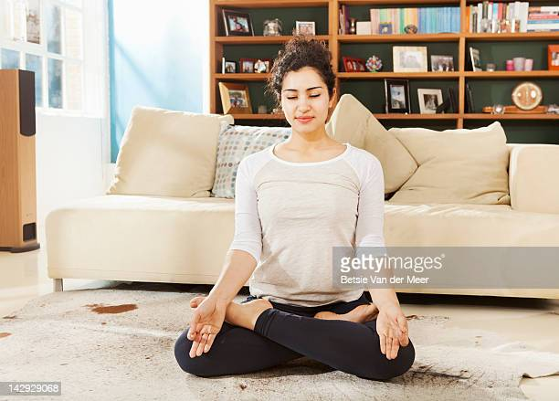 Woman relaxing in yoga pose in livingroom.