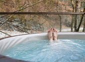 Woman relaxing legs in hot tub jacuzzi in nature
