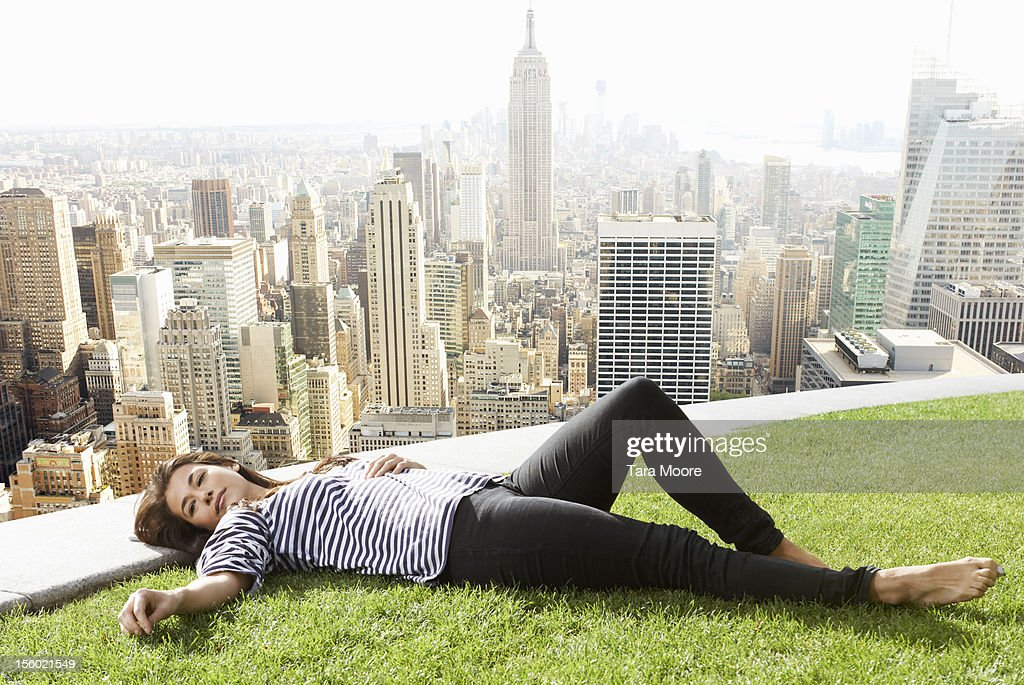 woman relaxing next to new york city skyline : Stock Photo