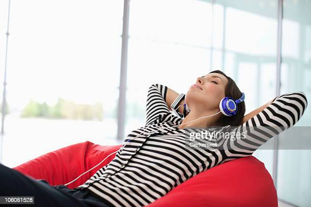 Woman relaxing on a bean bag while listening music through headphones