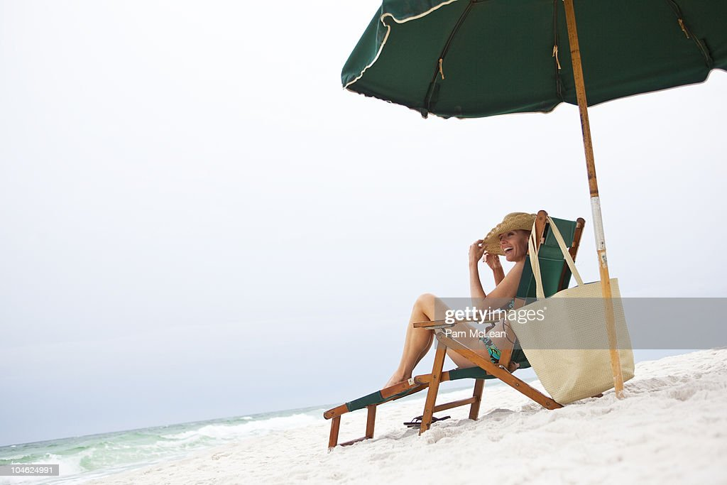 Woman relaxing on a sunlounger on the beach : Stock Photo