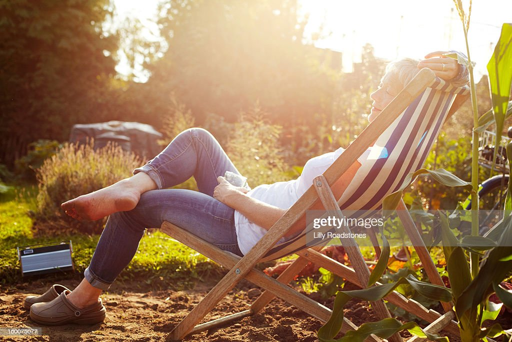 Woman relaxing on allotment : Stock Photo