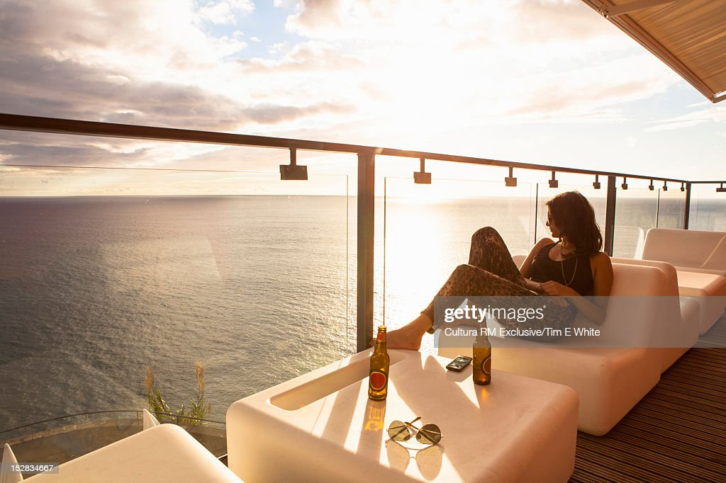 Woman relaxing on bar balcony : Stock Photo