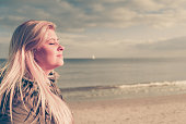 Leisure, spending free time outside, healthy walks concept. Woman wearing warm jacket relaxing on beach near sea, cold sunny day