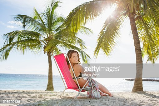 Woman relaxing on beach lounger : Bildbanksbilder