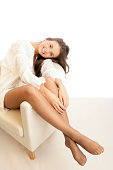 Young woman in stockings sitting on armchair