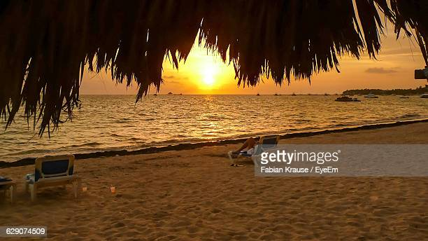Woman Relaxing On Deck Chair At Beach Against Sky During Sunset