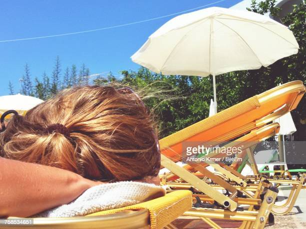 Woman Relaxing On Deck Chair At Poolside During Sunny Day