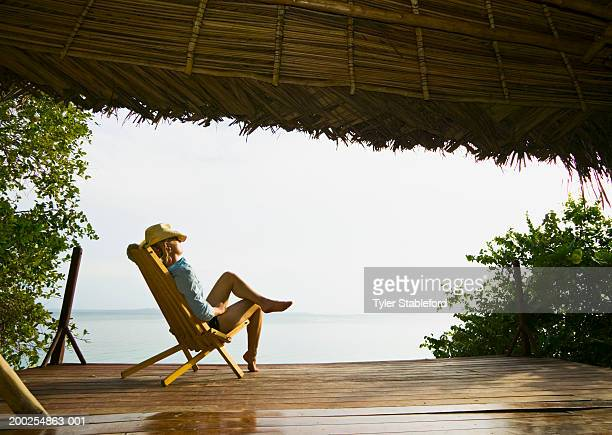 Woman relaxing on deck of seaside bungalow, side view