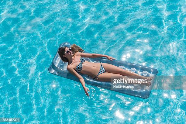 Woman relaxing on inflatable float mattress, pool