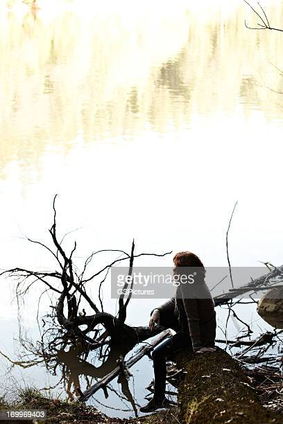 Woman relaxing on log in nature