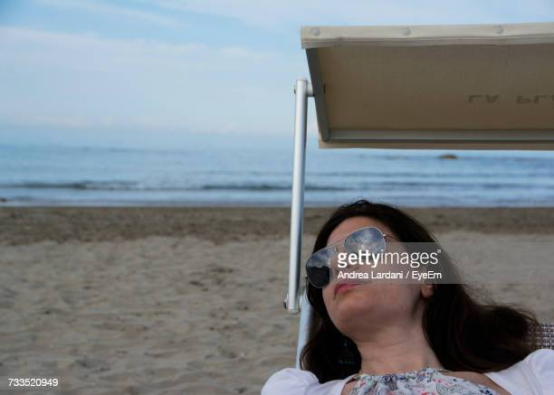 Woman Relaxing On Lounge Chair At Beach